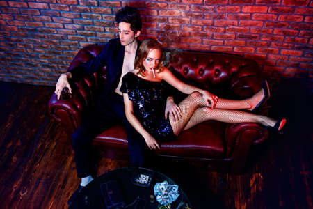 Glamorous couple of young people spending time at night club or casino. Entertainment industry. Beauty, fashion concept. Stock Photo