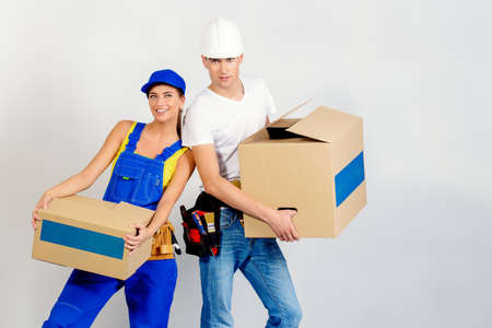 Portrait of a happy man and woman move to a new apartment, they carry boxes with things. Repair, construction and mortgage concept. Banco de Imagens