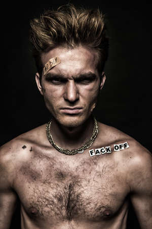Bad boy concept. Close-up portrait of a bad guy showing rudeness and aggression. Rocker, punk. Stock Photo