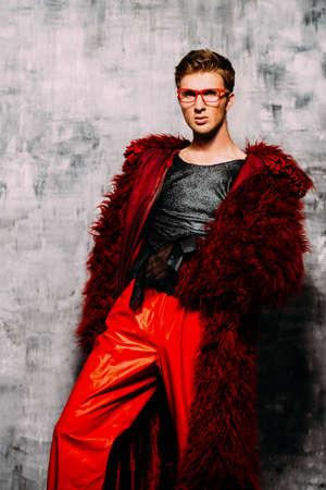 Vogue shot. Handsome male model posing in long red fur coat. Mens beauty, fashion. Studio shot. Stock Photo