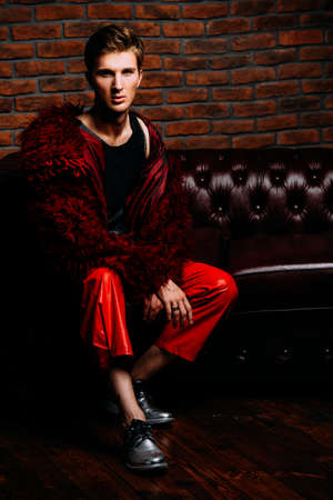 Vogue shot. Imposing fashion male model posing in long red fur coat and designer clothing. Mens beauty, fashion. Luxurious apartments. Stock Photo