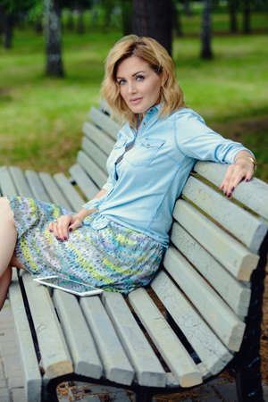 Happy middle aged woman relaxing on a bench in the park on a summer day. Mood of summer and carefree vacations. Beauty, cosmetics. Stock Photo