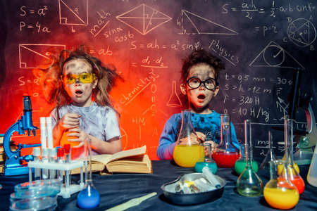 Funny little children doing experiments in the laboratory.