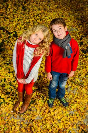 Two cheerful kids in a beautiful autumn park. Childrens fashion. Autumn leaf fall.