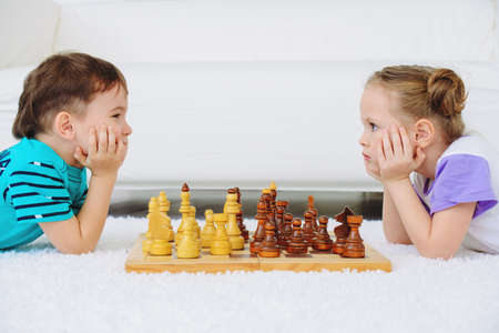 Children playing chess at home.