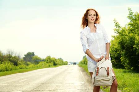 高速道路の上に立って、通過する車を引く魅力的な若い女性。 写真素材