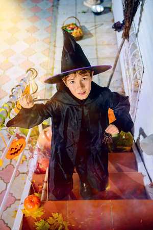 A boy in a costume of wizard with his magic wand is going to a halloween party.