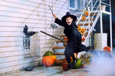 Ein Junge in einem Kostüm des Assistenten auf einem Besen mit seinem Zauberstab fliegen. Süßes oder Saures. Halloween-Feier.