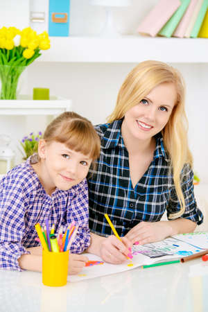 Happy family at home. Mother and daughter drawing and do lessons together. Education.