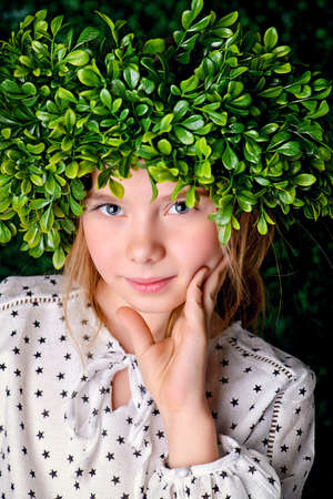 Portrait of a beautiful summer girl wearing green wreath in a green summer garden. Childrens fashion. Фото со стока