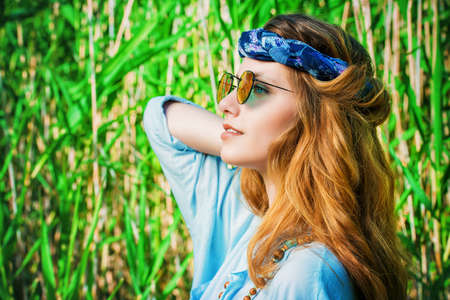 La belle fille hippie se trouve parmi les roseaux lors d'une journée ensoleillée d'été. Esprit de liberté. Tir de mode. Bohème, style bo-ho. Banque d'images - 82434591