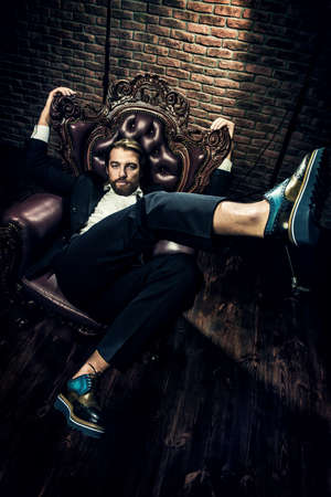 Portrait of a stylish handsome man on a vintage armchair. Fashion shot. Mens clothing and accessories.