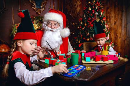 산타 클로스와 엘프는 크리스마스에 아이들을위한 선물을합니다. 산타 클로스의 워크샵. 크리스마스 개념입니다.