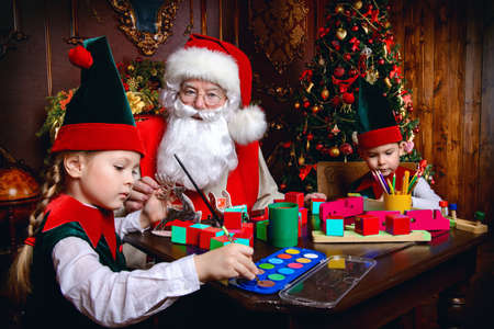 Santa Claus and the elves make gifts for children at Christmas. Workshop of Santa Claus. Christmas concept. Banco de Imagens