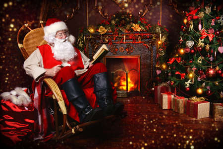 Good old Santa Claus having a rest in his house next to the fireplace and Christmas tree. Standard-Bild