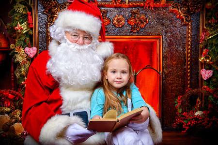 良い古いサンタ クロースと童話を読む小さな女の子。クリスマス ツリーと暖炉のある部屋は、クリスマスの装飾。