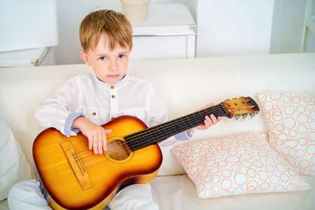Cute five year old boy learns to play the guitar at home.