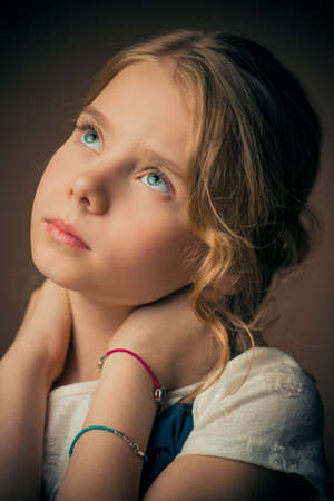 Portrait of a beautiful eight year old girl with calm pensive look. Childhood concept.