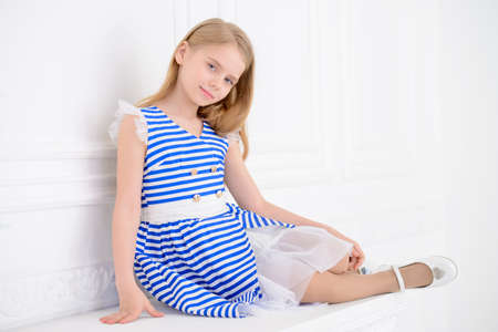 Cute little girl in a beautiful summer dress posing in a room with classical interior. Kids fashion.