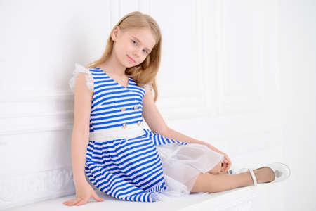 Niña linda en un hermoso vestido de verano posando en una habitación con el interior clásico. Moda para niños. Foto de archivo - 82599972