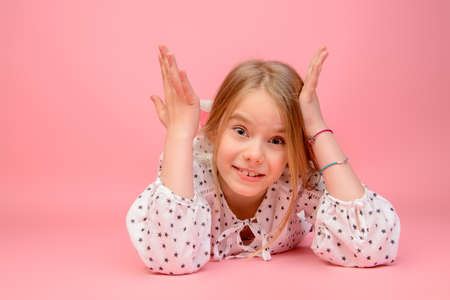 Happy childhood. Cute eight year old girl laughing at camera. Studio shot. Pink background.