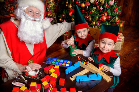 Santa Claus and the elves make gifts for children at Christmas. Workshop of Santa Claus. Christmas concept. Stock Photo