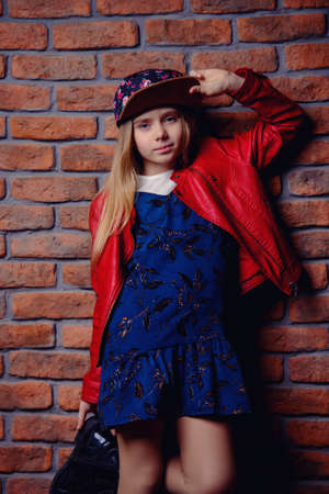 Modern eight year old girl posing by the brick wall. Urban style clothes. Childrens fashion. Reklamní fotografie