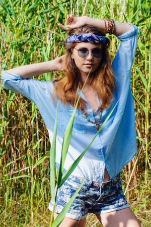 Beautiful hippie girl stands among the reeds in a summer sunny day. Spirit of freedom. Fashion shot. Bohemian, bo-ho style.