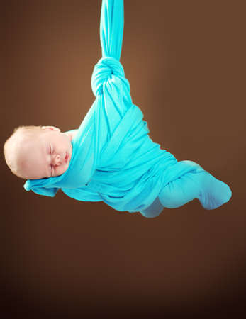 Sweet sleeping baby wrapped in a blanket. Baby care, healthcare. Stock Photo