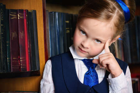 Portrait of a cute little girl standing by bookshelves in the library. Educational concept.