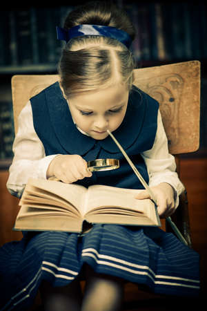 Cute girl looks curiously into the book in a library. Educational concept.