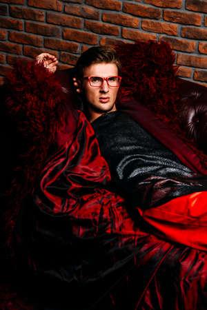 부식 긴 빨간 모피 코트와 디자이너 의류에 포즈 패션 남성 모델.