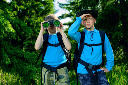 Two boys friends go hiking with backpacks.
