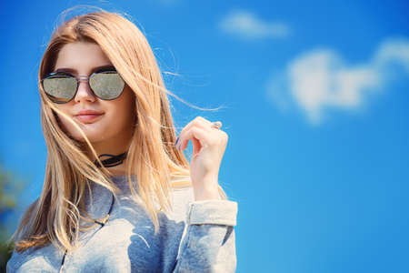 Youth style. Modern girl teenager with long blonde hair posing in sunglasses over blue sky. Beauty, fashion.