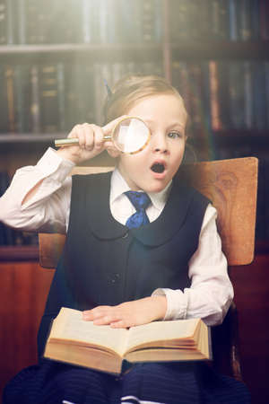 Cute girl looks curiously through a magnifying glass in a library. Educational concept. Stock Photo