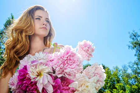 Portrait of a beautiful young woman with a bouquet of fresh summer flowers outdoor. 版權商用圖片