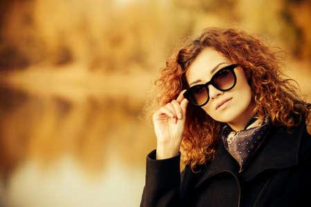 가을 스타일. 아름 다운 젊은 여자 선글라스와 검은 코트를 입고 밝은 폭시 머리. 아름다움, 패션.