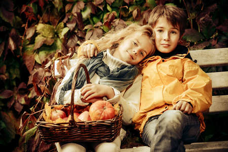 Happy romantic boy and girl sitting on a bench in a beautiful autumn park. Childrens fashion. Autumn mood, halloween. Sepia. Stock Photo