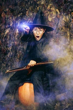 Ein Junge in einem Kostüm des Assistenten mit seinem Zauberstab zaubert mit magisches Buch. Halloween-Konzept. Standard-Bild - 83419778