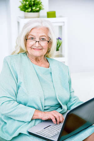 Contemporary senior woman working with laptop at home.