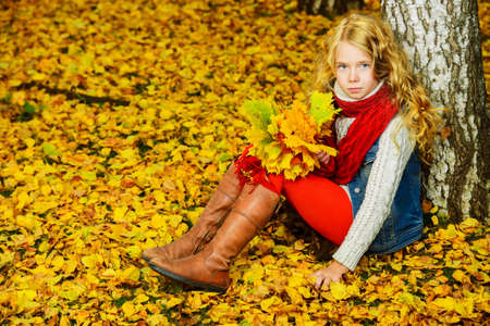 Pretty girl with a bunch of yellow leaves in the beautiful autumn park. Childrens fashion.