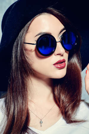 Close-up portrait of a hipster girl wearing hat and round sunglasses. Beauty, cosmetics. Stock Photo