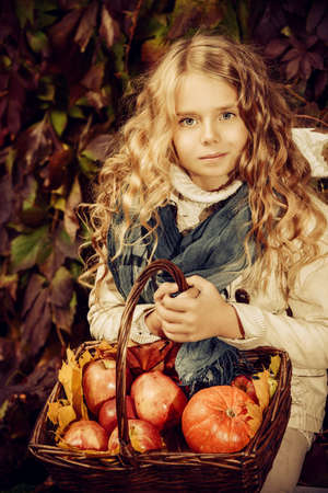 Lovely little girl sitting on a bench with a basket of red apples in a beautiful autumn park. Childrens fashion. Sepia. Stock Photo