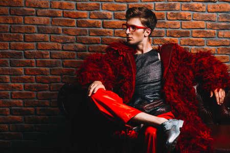 유행 쐈어. 부식 긴 빨간 모피 코트와 디자이너 의류에 포즈 패션 남성 모델. 남자의 아름다움, 패션. 호화로운 아파트.