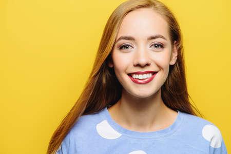 Joyful young woman with beautiful smile posing over yellow background.