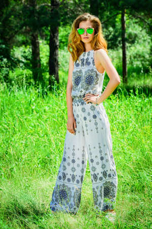 Beautiful romantic girl in a clearing in the forest. Modern hippie style. Banco de Imagens
