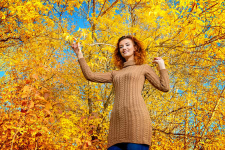 Beautiful dreamy girl with curly red hair walks in autumn park. The mood of autumn, leaf fall. Autumn fashion.
