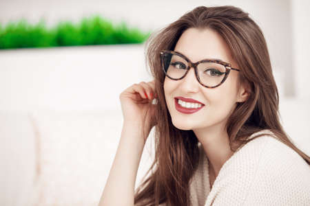 Beautiful smiling woman at home. Beauty, fashion. Optics style. 版權商用圖片
