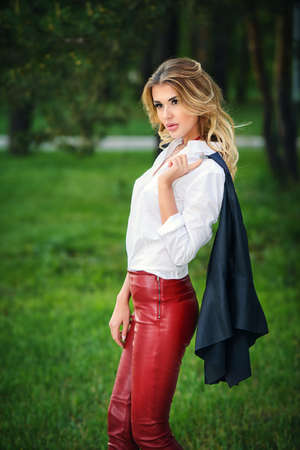 Fashionable gorgeous woman wearing red leather trousers and white blouse posing at a park.