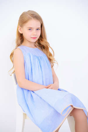 Beautiful little girl in a pale blue dress standing in a white room full of light. Kids fashion. Hairstyle.
